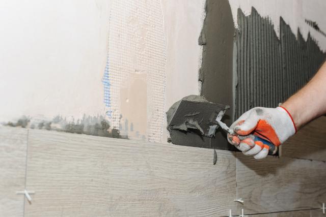 Worker installing ceramic tile in Gresham